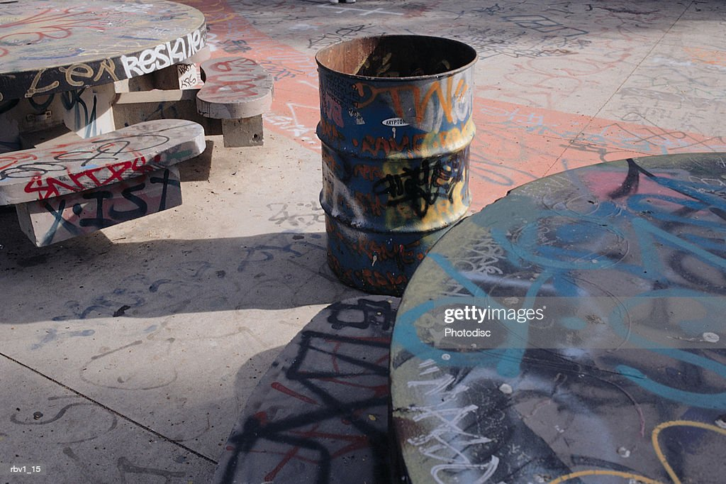 stone table and benches covered in graffiti with an oil drum for a garbage can : Foto de stock
