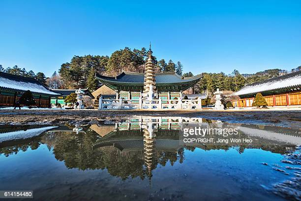 A stone tower and shrine buildings in Korean Buddhist temple with reflections