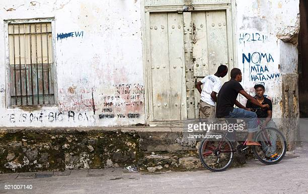 stone town, zanzibar: three young men with bike chatting - black alley stock photos and pictures