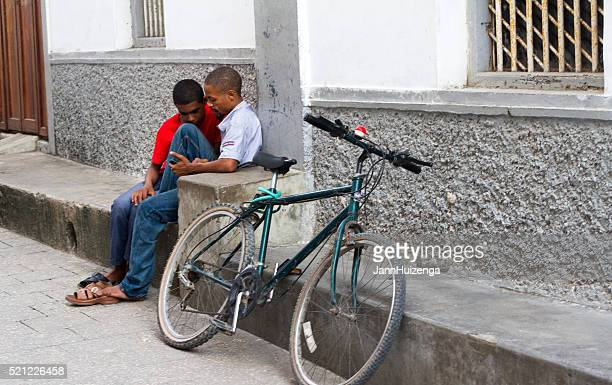 Stone Town, Zanzibar: Two Young Men Looking at Phone