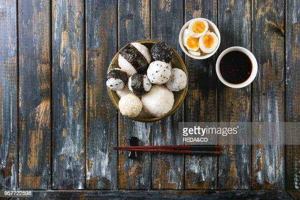 Stone tray with different size rice balls with black sesame and seaweed nori served with soft boiled eggs soy sauce chopsticks over wooden plank...