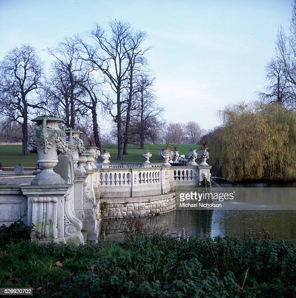 Stone urns punctuate an ornamental balustrade which encloses a water garden in Kensington Gardens London England