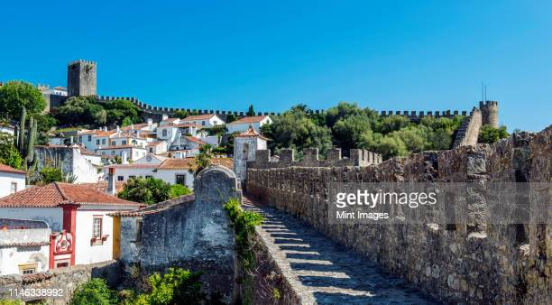 stone walkway and obidos cityscape, leiria, portugal - leiria photos et images de collection