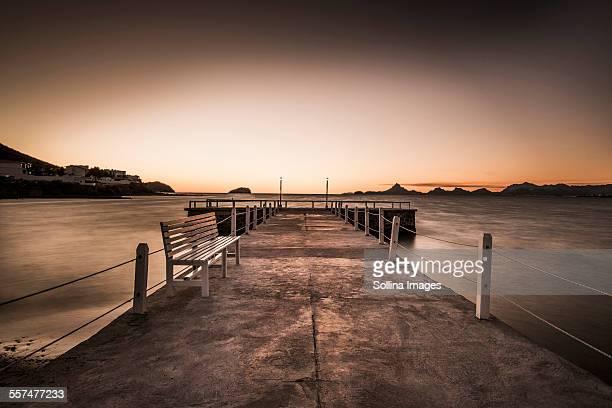 Stone walkway and ocean waves under sunset sky