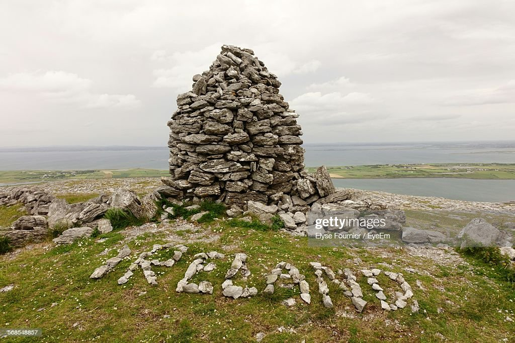 Stone Wall And Text On Field In Front Of Sea Against Cloudy Sky : Stock Photo