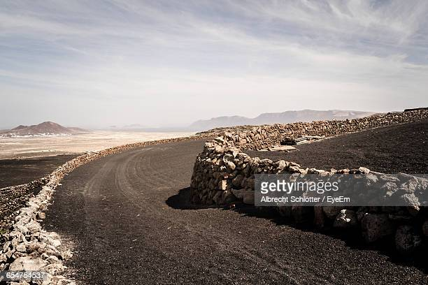 stone wall by road against sky - albrecht schlotter foto e immagini stock