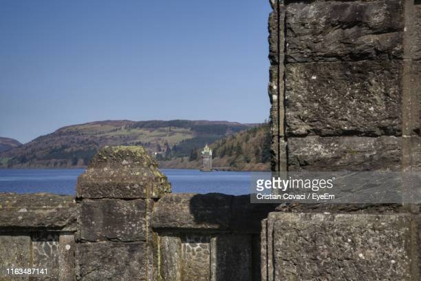 stone wall by sea against clear blue sky - lake vyrnwy stock pictures, royalty-free photos & images