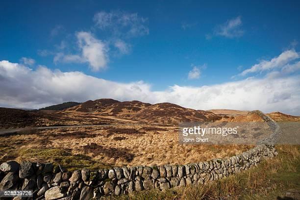 A stone wall going across a landscape; dumfries scotland
