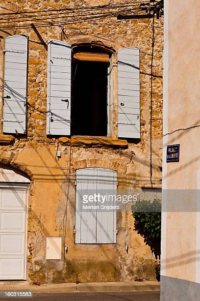 stone wall with blue window shutters - bedarrides photos et images de collection