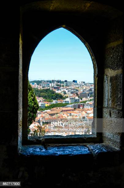 a stone window frames a city on a hill - brian sills stock pictures, royalty-free photos & images