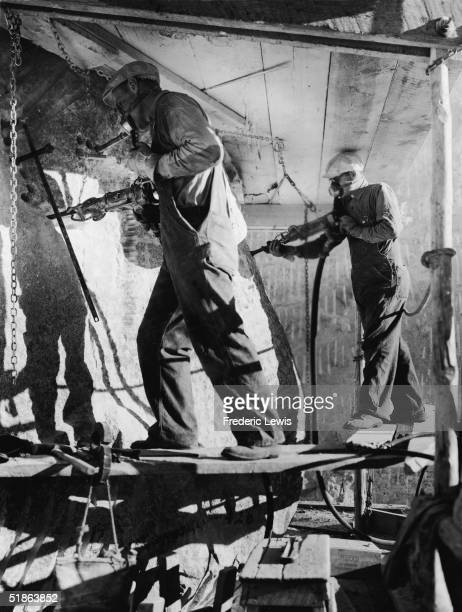 Stone workers carve the eyes of President Theodore Roosevelt with air hammers during the construction of the Mount Rushmore National Memorial in the...