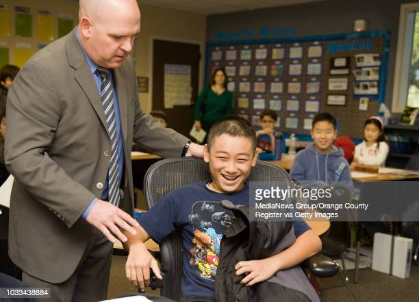 Stonegate Elementary School principal Stan Machesky awards sixth grader Joyee Chen his chair as part of a monthly awards program PBIS Positive...