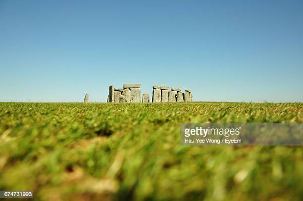 Stonehenge On Grassy Field Against Clear Sky