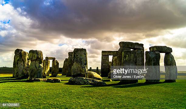 Stonehenge On Grassy Field Against Cloudy Sky At Sunset