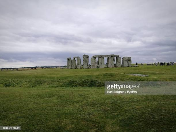 Stonehenge On Grassy Field Against Cloudy Sky