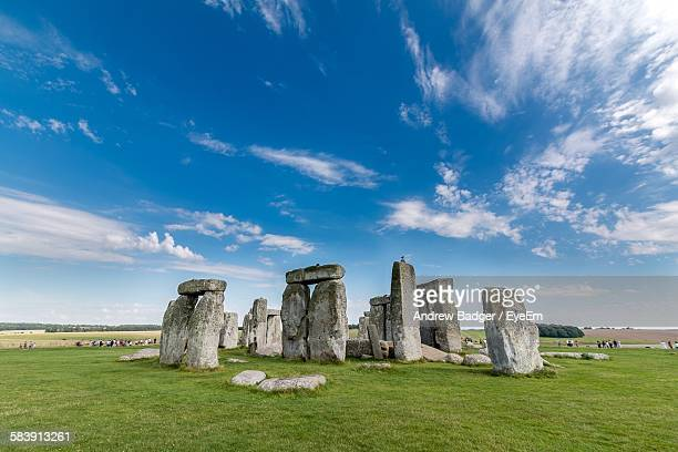 stonehenge on grassy field against sky - stonehenge stock photos and pictures