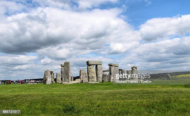 Stonehenge On Grassy Field Against Sky