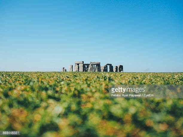 Stonehenge On Grassy Landscape Against Clear Sky