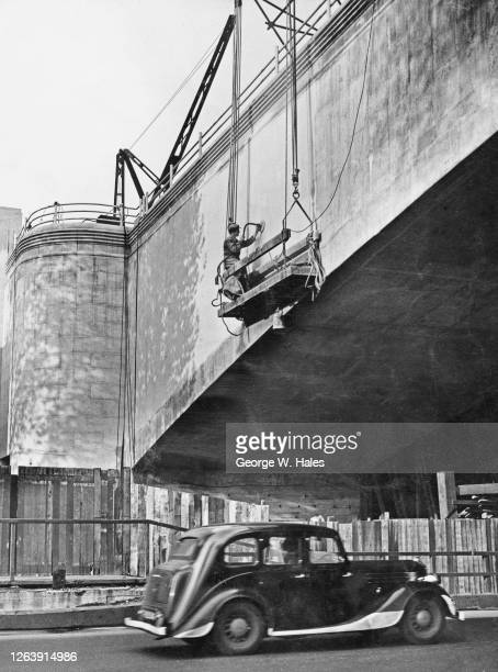 Stonemason at work in a cradle, using an electric grindstone put a smooth finish on the surface of Waterloo Bridge over the River Thames in London,...