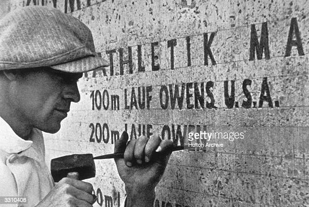A stonemason carving the name of Jesse Owens and other winners of the 1936 Berlin Olympics into a wall on one side of the Marathon Gate in Berlin