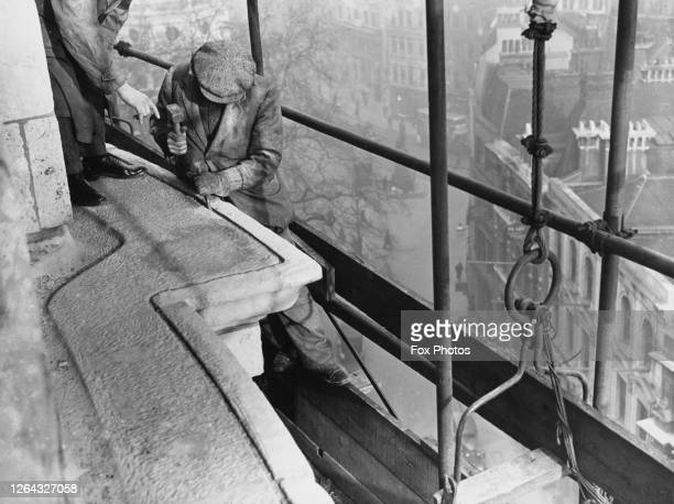 Stonemason channelling the cornice on the roof of St Paul's Cathedral prior to fitting a covering of asphalt over the stone to preserve it as well as...