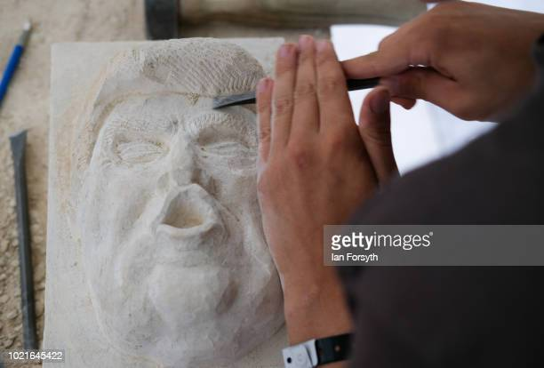 Stonemason Henrik Storksen from Norway works on his sculpture of Donald Trump as he takes part in a stone carving festival at York Minster on August...