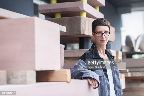 stonemason leaning against block of stone looking at camera - sigrid gombert stock-fotos und bilder