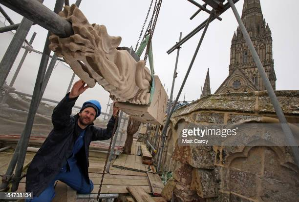 Stonemason Matt Barton holds the new gargoyle he carved as it is fixed to the Chapter House roof at Salisbury Cathedral on October 25, 2012 in...
