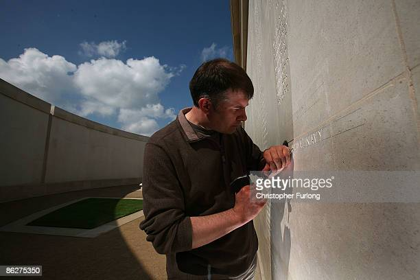 Stonemason Nick Hindle begins to add the latest names of 67 servicemen and women to the Armed Forces Memorial at the National Memorial Arboretum on...