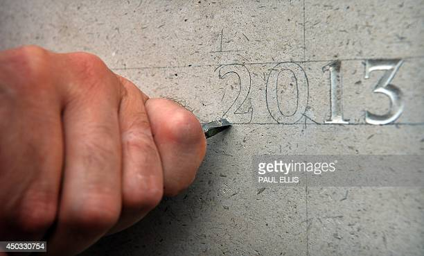 Stonemason Nick Hindle begins to carve the names of British service men and women who died died in the line of duty or in an act of terrorism in 2013...