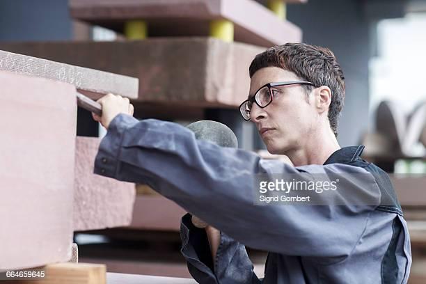 stonemason using chisel and mallet on block of stone - sigrid gombert stock-fotos und bilder