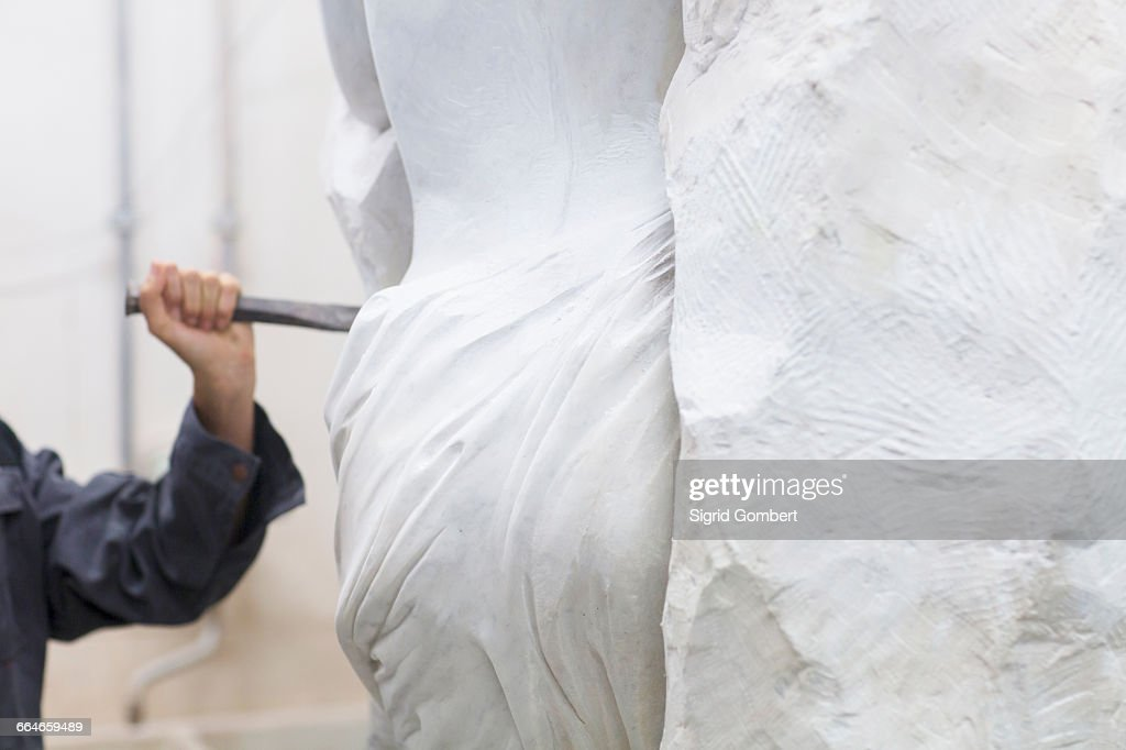 Stonemason using chisel and mallet to create sculpture : Stock Photo