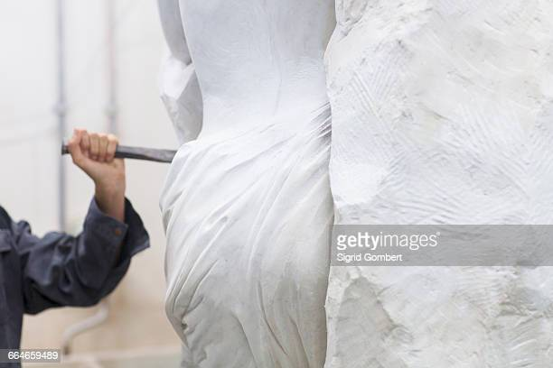 stonemason using chisel and mallet to create sculpture - sculptuur stockfoto's en -beelden