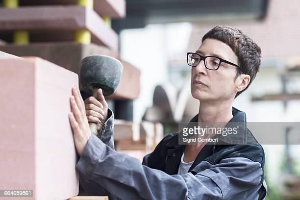 stonemason using mallet checking block of stone - sigrid gombert stock-fotos und bilder