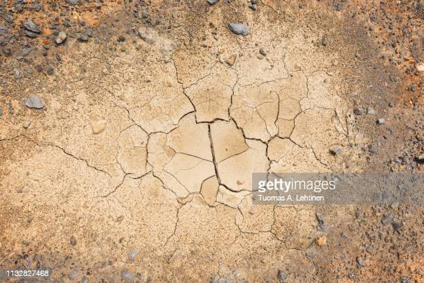 stones and dry and cracked soil ground during drought, viewed from above with vignette. - lehm mineral stock-fotos und bilder