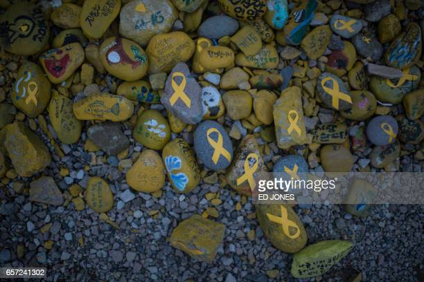TOPSHOT Stones emblazoned with yellow ribbons are displayed near the makeshift homes of relatives of Sewol ferry victims at Paengmok harbour on South...