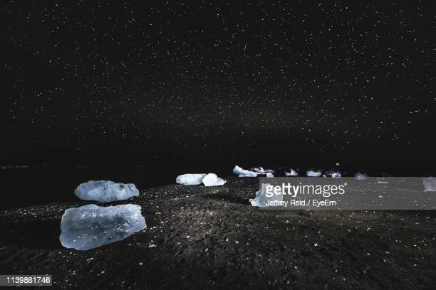 Stones On Snow Covered Land Against Sky At Night