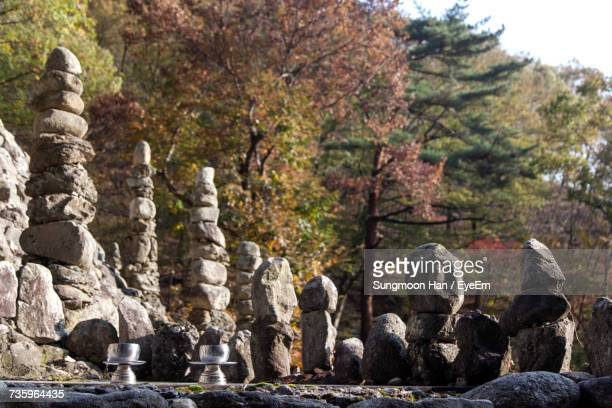 stones stacked by oil lamps against autumn trees at tapsa temple - jeonju stock pictures, royalty-free photos & images