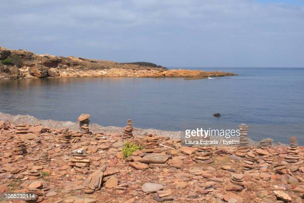 Stones Stacked On Sea Shore Against Sky