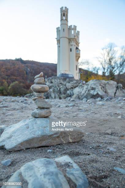 Stones stacked on top of each other seen on a path as a result on low water next to the Mouse Tower on November 13 2018 in Bingen Germany Summer heat...