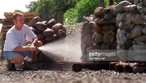 LSStoneshose4KH8/22/96Matt Huddleston sales manager at Country Garden Nursery in Placentia hoses down Arizona Lodi Lomita and River Rock cobblestones...