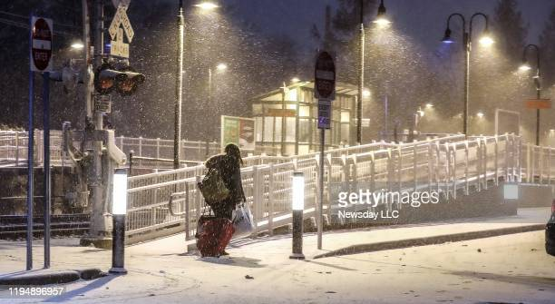 A Long Island Rail Road rider crosses the tracks at the Stony Brook Long Island station as a sudden snow squall passed over the north shore of Long...