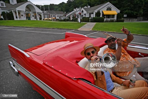 Musicians Thomas Manuel, trumpet, and Ellis B. Holmes III, drums, travel between gigs in a classic 1957 Plymouth convertible as they perform in...