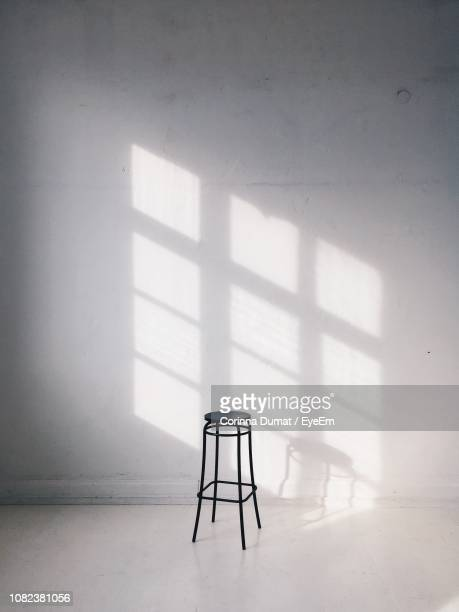 stool against white wall at home - stool stock pictures, royalty-free photos & images