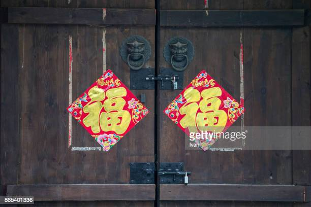 Stool and wooden door of traditional house with Chinese New Year spring couplet couplet
