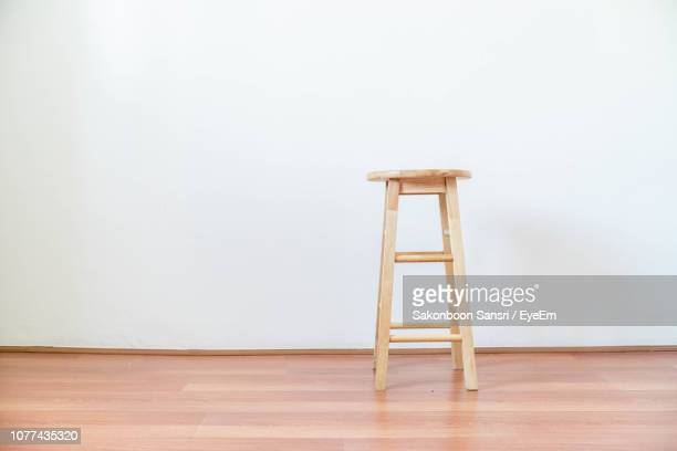 stool on hardwood floor against white wall - step ladder stock photos and pictures