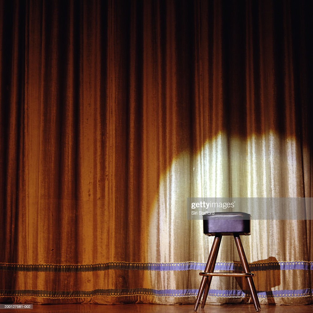 Stool sitting on stage in front of gold curtain : Bildbanksbilder