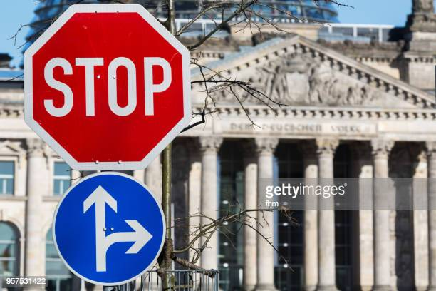 stop- and arrow-sign and reichstag building in the background (berlin, germany) - demokratie stock-fotos und bilder