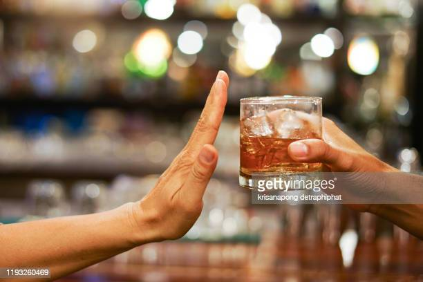 stop drinking,stop drinking conceptman alcoholic social problems sitting at table refusal of alcohol say no to addiction close-up - alcohol drink stock pictures, royalty-free photos & images