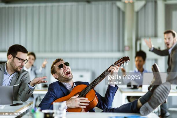 stop playing that guitar, we cannot work! - irritation stock pictures, royalty-free photos & images